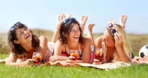 A group of friends lying on a blanket outside and enjoying a drink together