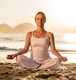 Young woman sitting in lotus position on the beach and meditating.