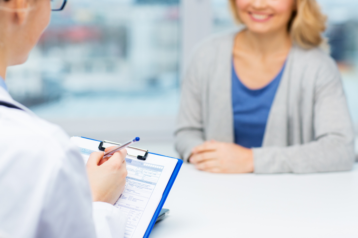 medicine, health care and people concept - close up of doctor with clipboard and young woman patient meeting at hospital